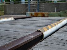 Rusty railroad track on wooden dock next to barrier stock images