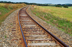 Rusty railroad tracks on a railway embankment between meadows Royalty Free Stock Images