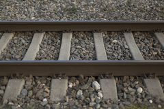 Rails and crushed stone closeup background. Rusty rails and gray crushed stone closeup background Stock Images