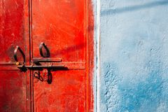 Old rusty red metal door and blue wall