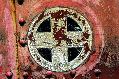Rusty red plus add cross sign symbol on old metal background tex. Rusty red plus add cross sign symbol background texture from an old metal train car Royalty Free Stock Image