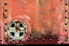Rusty red plus add cross sign symbol on old metal background tex. Rusty red plus add cross sign symbol background texture from an old metal train car Royalty Free Stock Photo