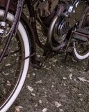 Rusty motorized retrofit bicycle with white wall tires. A rusty red purple motorized retrofit bicycle with white wall tires royalty free stock image