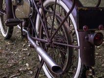 Rusty motorized retrofit bicycle with white wall tires. A rusty red purple motorized retrofit bicycle with white wall tires stock photos