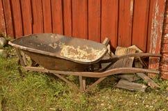 Rusty red wheelbarrow. Vintage rusty old wheelbarrow left along a red fence royalty free stock photos