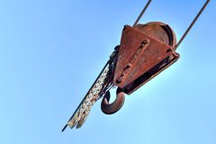 Rusty Redundant Lifting Gear with Blue Sky. Old industrial crane hook covered in rust horizontal perspective with blue sky as background Stock Images