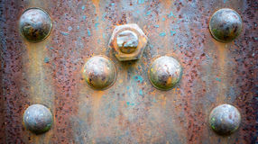 Rusty Riveted Steel Background. A close up view of a corroded metal iron steel with rivets and bolts on it. Great for desktop wallpapers and backgrounds Royalty Free Stock Images