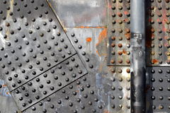 Rusty rivets with pipe. Riveted steel plates with pipe and rust Stock Images