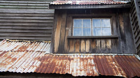 Rusty roof. A view of a rusty roof of a house with worn, weathered unpainted walls and wood panels. Photo taken on November 13th, 2014 Royalty Free Stock Photography