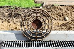 Rusty round hatch and grate for rainwater on the side of the city road. repair and expansion of the road. reportage photography.  stock image