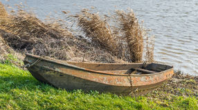 Rusty rowing boat at the bank of a lake Stock Images