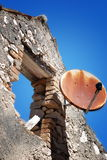 Rusty satellite dish on abandoned ruined house in Susak Royalty Free Stock Photo