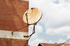 Rusty satellite dish on the outside wall Stock Photos