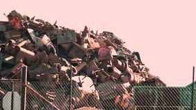 Rusty scrap metal in a heap through a fence stock video footage