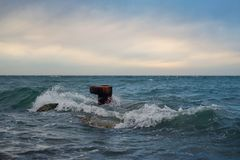 Rusty sea bollard. Surrounded by the waves in the sea stock image
