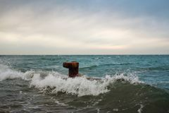 Rusty sea bollard. Surrounded by the waves in the sea stock images