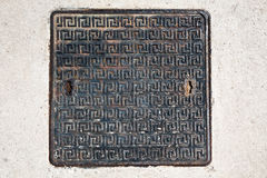 Rusty sewer. Square metal sewer hatch with light rust on the concrete surface royalty free stock photos