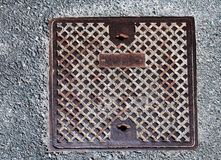 Rusty sewer lid on concrete pavement Stock Images