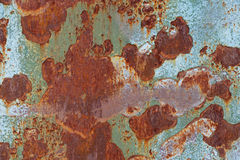 Rusty shabby metallic sheet with peeling green paint. Metal texture Stock Images