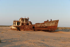 Rusty ship of Aral Sea fishing fleet. Rusty ship lying in the sand at the former Soviet Aral Sea port of Moynaq in Uzbekistan stock image