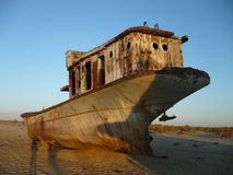 Rusty ship on the bottom of the Aral Sea. Cemetery ships on the dried-up bottom of the Aral Sea, which turned into a desert, shows the largest environmental Royalty Free Stock Images