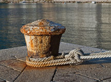 Rusty ship mooring. Port of detail - the waterfront old rusty metal wedge ( with a boat mooring ropes) with orange-yellow light of sunset near the Adriatic Sea ( stock photo