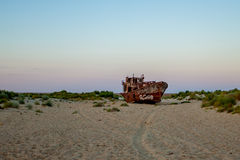 The rusty ship is on the sand. Big rusty ship is at the bottom of the Aral sea in the town of Muynak in Uzbekistan. On the ship with white paint painted mermaid Royalty Free Stock Photography