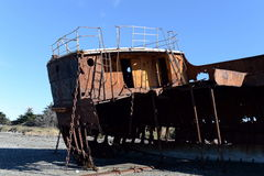Rusty ship on the shore of the Strait of Magellan in the village of San Gregorio. Royalty Free Stock Images