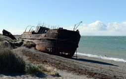 Rusty ship on the shore of the Strait of Magellan in the village of San Gregorio. Royalty Free Stock Image