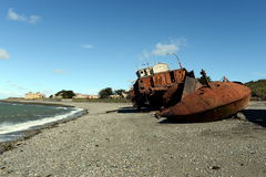 Rusty ship on the shore of the Strait of Magellan in the village of San Gregorio. Stock Images