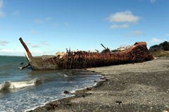 Rusty ship on the shore of the Strait of Magellan in the village of San Gregorio. Stock Image