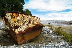 Rusty ship stranded aground on the beach with pebbles in the Black Sea. Rusty ship stranded aground on the beach in the Black Sea royalty free stock photography
