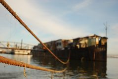 Rusty ship stranded to the shore. An old rusty craft stranded with a thick steel cable to the shore of the Danube, on a blue sky clear weather Royalty Free Stock Photography
