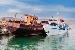 Rusty ship  and white ship. On the shore Stock Photography