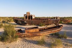 Rusty ships of the Aral Sea in Uzbekistan, after its waters have dried out. Rusty ships that have remained on the bottom of the Aral Sea in Uzbekistan Stock Photos
