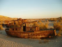 Abandoned rusty ships of the Aral Sea. Rusty ships on the dried-up bottom of the Aral Sea, which turned into a desert from unreasonable economic activity of a Royalty Free Stock Photos