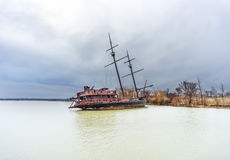 Rusty shipwreck marooned near shore on lake under a stormy blue Royalty Free Stock Images
