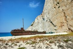 A rusty shipwreck on a rocky beach Royalty Free Stock Image