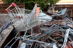 Rusty shopping trolley in recycling of ferrous material. For disposal Stock Photos