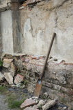Rusty shovel standing against old wall Royalty Free Stock Photo