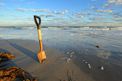 Rusty Shovel in Wet Sand at the Beach Royalty Free Stock Photo
