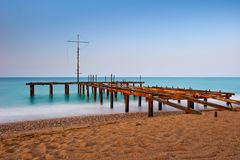 Rusty skeleton of the old pier and turquoise sea Royalty Free Stock Photo