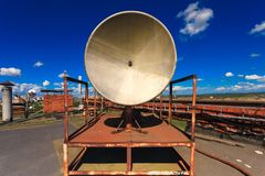 Rusty telecommunication tower with old satellite system consist of old satellite dish antenna is  located on the roof an. Rusty small telecommunication tower Royalty Free Stock Photos