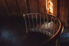 Rusty spiral stairs inside dark room Stock Photography
