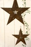 Rusty stars and ivy motif. Rusty, weathered metal stars with ivy motif on the side, on an off-white wall on a country home Royalty Free Stock Photo