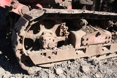 Rusty steel bulldozer track and wheels two stock image