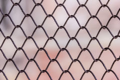 Rusty steel chain link or wire mesh as boundary wall. There is still concrete block wall behind the mesh. Stock Images
