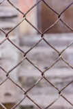 Rusty steel chain link or wire mesh as boundary wall. There is still concrete block wall behind the mesh. Royalty Free Stock Photos