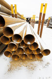 Rusty steel pipes in stacks on outdoor warehouse Stock Images