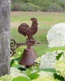 Rusty Steel Rooster Bell på ladugårdbräde med blommor och fältet Royaltyfria Bilder